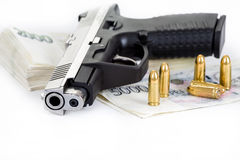 Gun with bullet and czech banknotes Royalty Free Stock Image