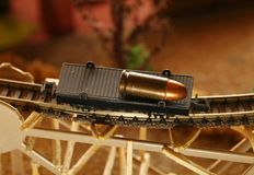 Gun bullet scene. The old and dirty pistol bullet put on the miniature flat wagon train toy background represent the weapon and train toy model concept related Royalty Free Stock Photo