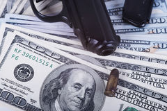 Gun with bullet on US dollar banknotes. Stock Image