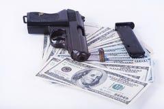 Gun with bullet on US dollar banknotes. Royalty Free Stock Photo