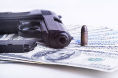 Gun with bullet on US dollar banknotes. Royalty Free Stock Photography