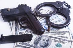 Gun with bullet on US dollar banknotes. Stock Photos