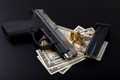 Gun with bullet on US dollar banknotes Royalty Free Stock Photos