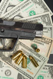 Gun with bullet on US dollar banknotes Stock Photos