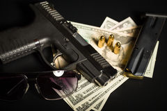 Gun with bullet on US dollar banknotes Royalty Free Stock Images