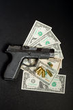 Gun with bullet on US dollar banknotes Royalty Free Stock Photos