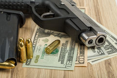 Gun with bullet on US dollar banknotes Stock Photography