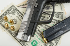 Gun with bullet on US dollar banknotes Stock Images