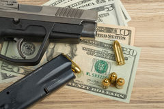 Gun with bullet on US dollar banknotes Royalty Free Stock Photo