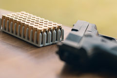 Gun with bullets. Handgun box with new ammunition. Royalty Free Stock Images