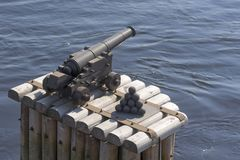 An ancient cannon and stacked cannon balls against the backgroun stock image
