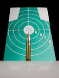 Gun cartridge over target with bulletholes Royalty Free Stock Images