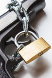 The gun, chain and closed padlock Royalty Free Stock Image