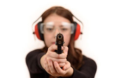 Gun. Close up young woman pointing a gun at the camera on white background stock image