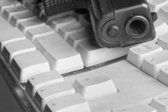 Gun And Computer Keyboard. Looking down the barrel of a pistol laid on the old dusty computer keyboard, in black and white Royalty Free Stock Images