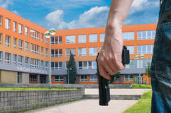 Gun control concept. Young armed man holds pistol in hand in public near school. Gun control concept. Young armed man holds pistol in hand in public place near Royalty Free Stock Photo