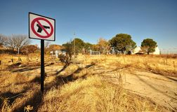 Gun Control. Sign at an abandoned site warning no firearms were allowed to be taken inside. Rural industrial/agricultural scene Stock Photography