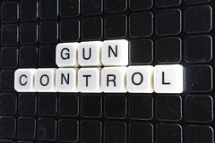 Gun control text word title caption label cover backdrop background. Alphabet letter toy blocks on black reflective background. Gun control royalty free stock photos