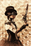 Gun cyberpunk. Portrait of a beautiful steampunk woman holding a gun over vintage background Stock Image