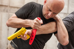 Gun Disarm. Self defense techniques against a gun point. Stock Image