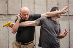 Gun Disarm. Self defense techniques against a gun point. Royalty Free Stock Photos