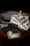 Gun and dollar bill in briefcase. Stock Photography