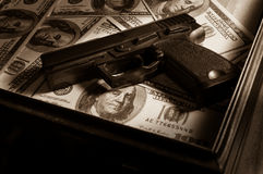 Gun on dollar bills in briefcase. Royalty Free Stock Image