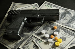 Gun and drug pills on dollar bills. Stock Photos