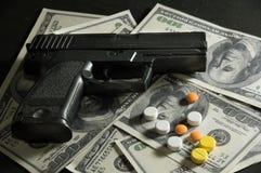 Gun and drug pills on dollar bills. Stock Photos