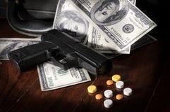 Gun and drug pills on dollar bills. stock images