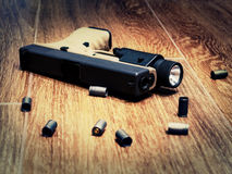 The gun on the floor. 9mm semi-auto pistol on the floor surrounded by spent shells, selective focus Royalty Free Stock Photo