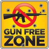 Gun Free Zone Assault Rifle Sign with Bullet Holes. Vector Gun Free Zone assault rifle street and building sign shot full of bullet holes Stock Photo