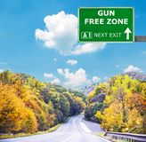 GUN FREE ZONE road sign against clear blue sky stock photography