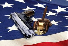 Gun with Gavel and Bullets on American Flag Royalty Free Stock Photography
