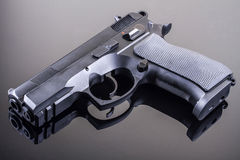 Gun on glass table. 9 mm hand gun on glass table with reflection Stock Image