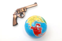 Gun on globe Stock Photo