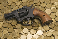Gun on gold coins Stock Images