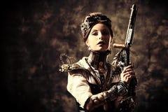 Gun grunge. Portrait of a beautiful steampunk woman holding a gun over grunge background Stock Photo