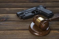 A gun and a hammer judge on the background of a wood texture table. royalty free stock photography