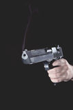 Gun in hand. Smoking gun after the shot in the hand of man Royalty Free Stock Photo