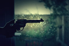 Gun in the hand. The gun in the hand on the dark background Royalty Free Stock Images