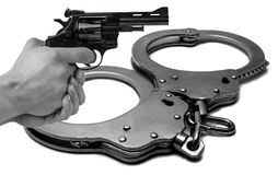 The gun in hand against the background of police handcuffs. just. The gun in hand against the background of police handcuffs. Adventure and justice Stock Photo