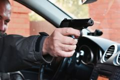 Killer in a car with a gun. The assassin shoots at point blank range
