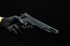 Gun and a Hand on a Black Royalty Free Stock Images