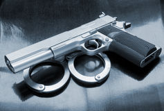 Gun and handcuffs Stock Image