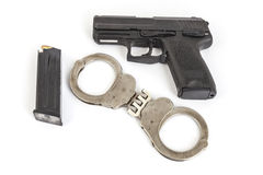 Gun and handcuffs. With white background Royalty Free Stock Photo