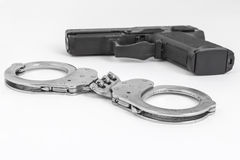Gun and handcuffs. With white background Stock Image