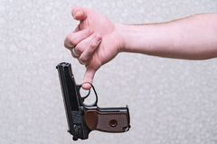 Gun hangs on a man`s finger on a gray background. The gun hangs on a man`s finger on a gray background. The gun is evidence royalty free stock photography