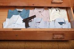 Gun hidden in a drawer full of shirt Stock Images