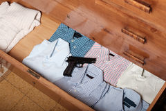Gun hidden in a drawer full of shirt at home. Clothes stock photo